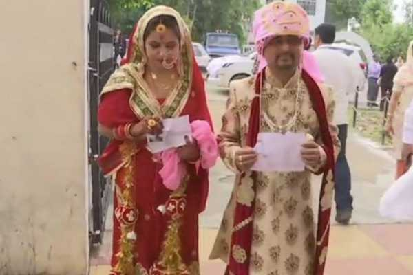 a-newly-married-couple-arrive-at-a-polling-station-in-udhampur-to-cast-their-votes